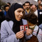 Woman with Photographs of Riot Victims